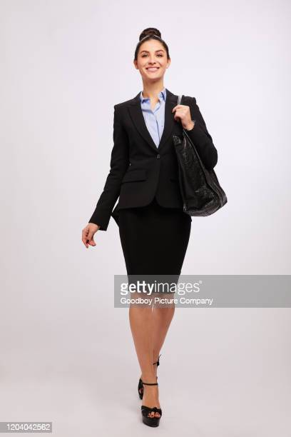 confident young businesswoman smiling while walking against a gray background - shoulder bag stock pictures, royalty-free photos & images