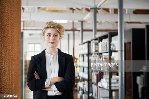 confident young businesswoman standing with her arms crossed in an office - 女性建築家 ストックフォトと画像