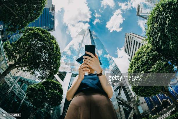confident young businesswoman using mobile phone in front of highrise financial towers in central business district on a fresh bright morning - customer engagement stock pictures, royalty-free photos & images