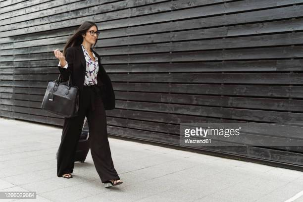 confident young businesswoman walking with luggage on footpath by black wall - black purse stock pictures, royalty-free photos & images