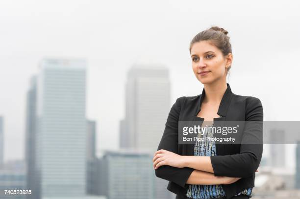 Confident young businesswoman with arms crossed on city office roof terrace, London, UK