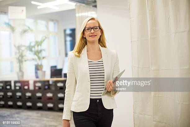 Confident young businesswoman with digital tablet in office