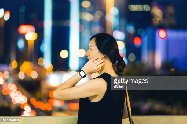 Confident young businesswoman with smart watch in urban city at night