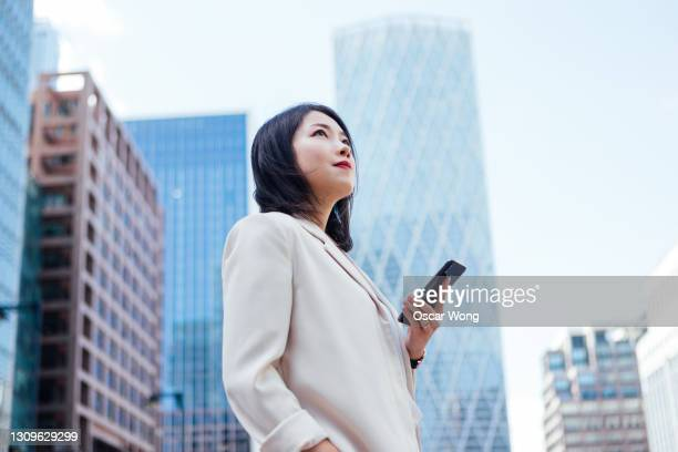 confident young businesswoman with smartphone standing against modern buildings - looking up stock pictures, royalty-free photos & images