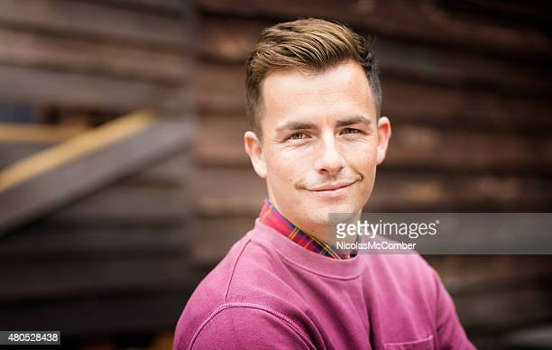 Confident young Englishman portrait in front of wooden wall