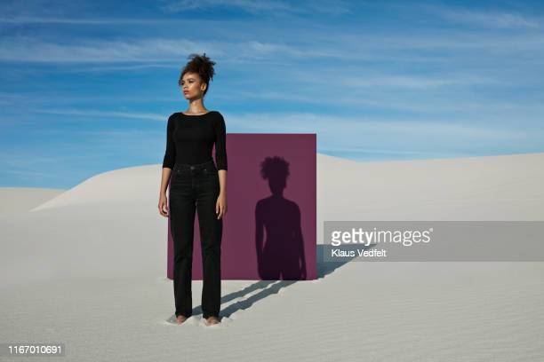 confident young fashion model standing against purple placard at white desert - cuadrado forma bidimensional fotografías e imágenes de stock