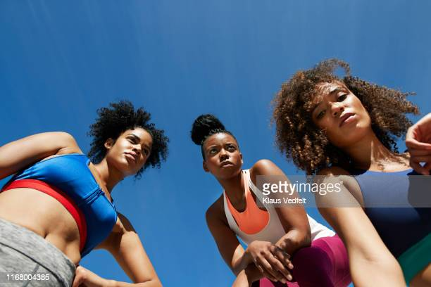 confident young female athletes against blue sky on sunny day - コイリーヘア ストックフォトと画像
