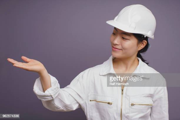 Confident young female construction worker gesturing against purple background