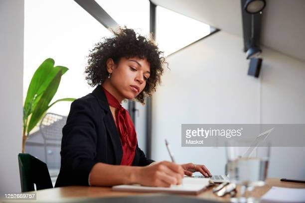 confident young female financial advisor writing on diary while sitting with laptop at desk in office - 金融関係の職業 ストックフォトと画像