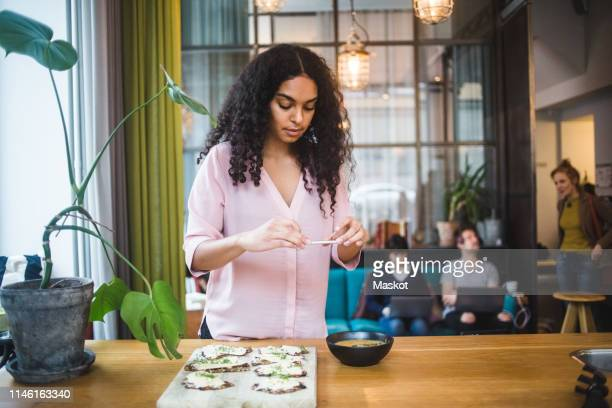 confident young female influencer photographing pumpkin soup and crispbread on table through smart phone at creative off - photography themes stock pictures, royalty-free photos & images