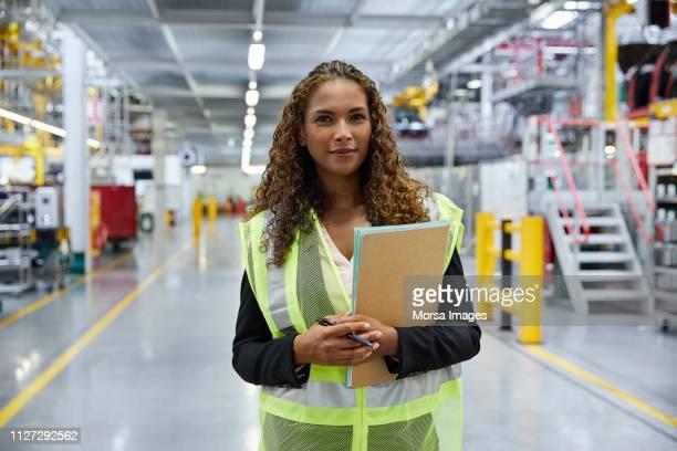 überzeugt junge weibliche supervisor mit dokument - maschinenbau stock-fotos und bilder
