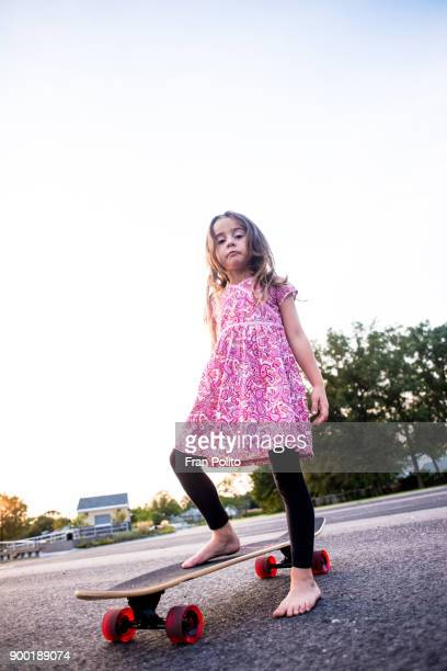 a confident young girl standing on her skateboard. - toughness stock pictures, royalty-free photos & images
