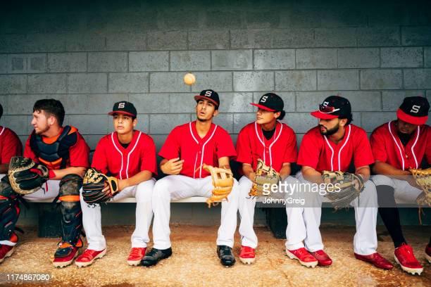 ダッグアウトに座っている自信のある若いヒスパニック系野球選手 - 高校野球 ストックフォトと画像
