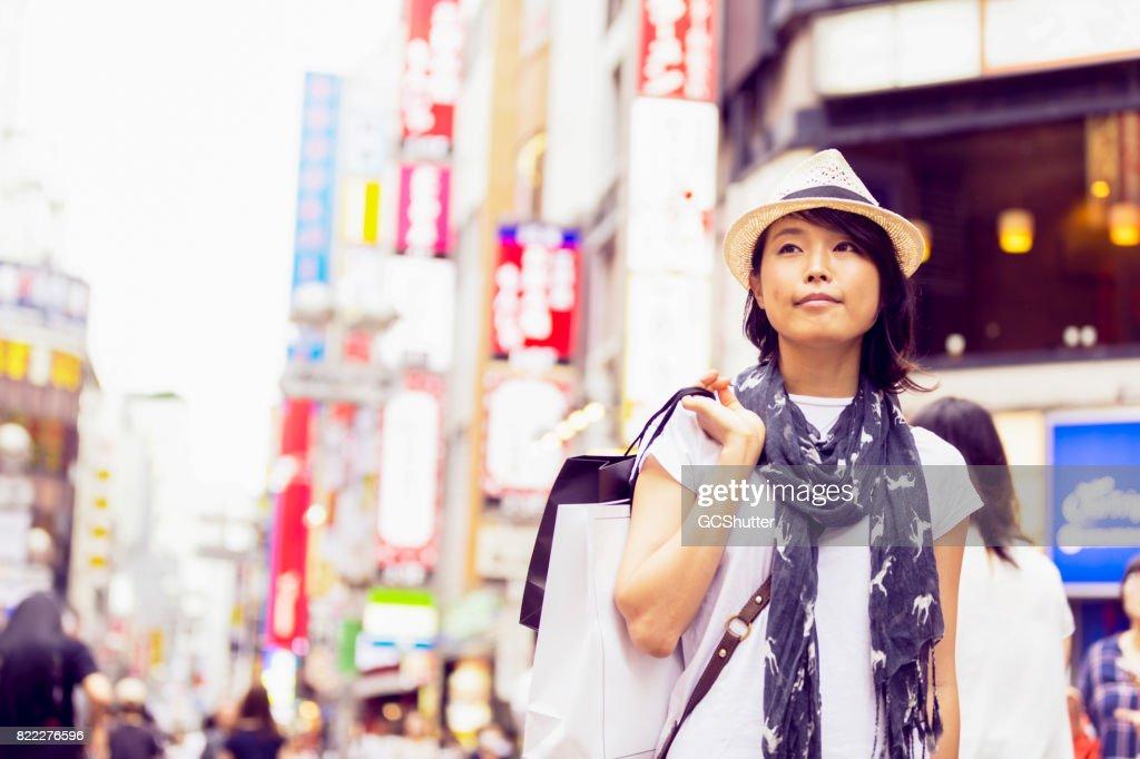 Confident young Japanese woman shopping at the Shibuya Ward : Stock Photo