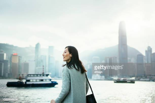 confident young lady looking forward to start her day on a fresh bright morning while standing against hong kong cityscape - mercato luogo per il commercio foto e immagini stock