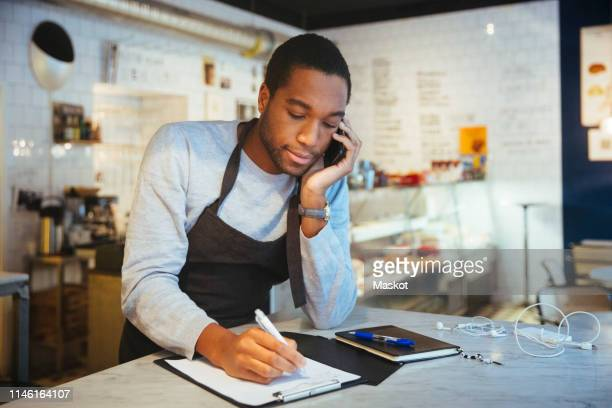 confident young male employee talking through smart phone while writing on clipboard at delicatessen - geschäftsinhaber stock-fotos und bilder