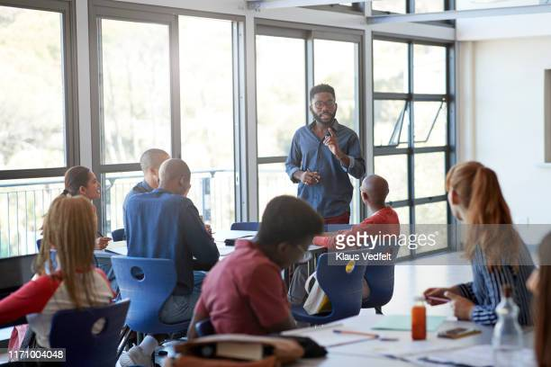 confident young male professor explaining students - instructor stock pictures, royalty-free photos & images