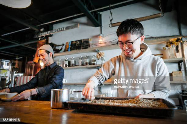confident young males happy cafe owner - ミッドアダルト stock pictures, royalty-free photos & images