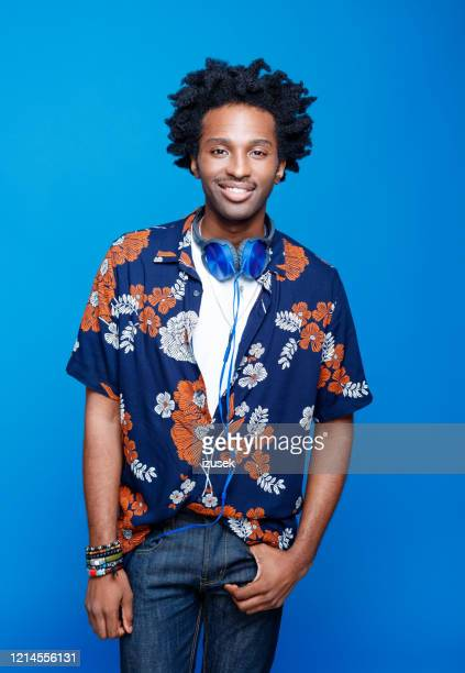 confident young man in hawaiian shirt on blue background - floral pattern stock pictures, royalty-free photos & images
