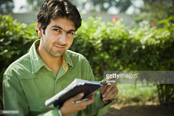 Confident young man in outdoor with diary looking at camera.