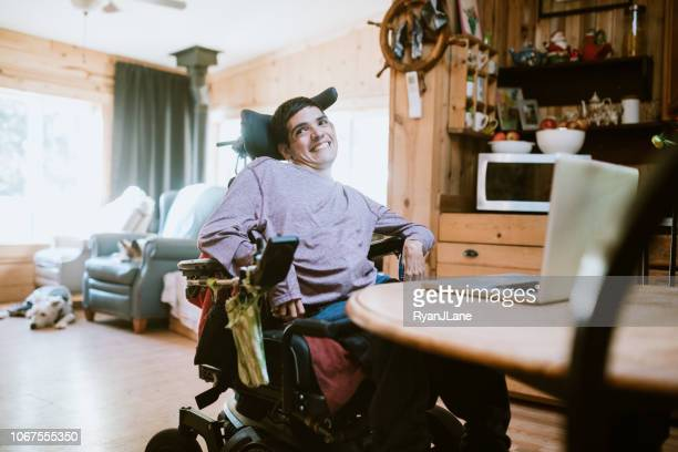 confident young man in wheelchair at home - independence stock pictures, royalty-free photos & images