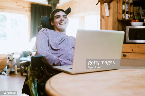 confident young man in wheelchair at home - persons with disabilities stock pictures, royalty-free photos & images