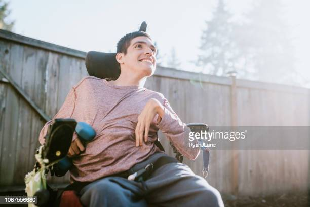 confident young man in wheelchair at home - respect stock pictures, royalty-free photos & images