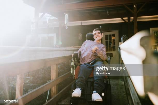 Zuversichtlich, junger Mann im Rollstuhl zu Hause