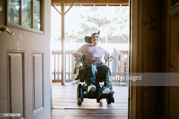 confident young man in wheelchair at home - assistive technology stock photos and pictures