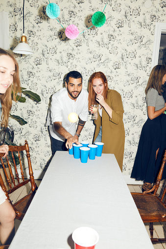 Confident young man playing beer pong on table by female friend at dinner party - gettyimageskorea