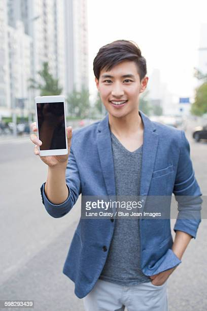 Confident young man showing smart phone