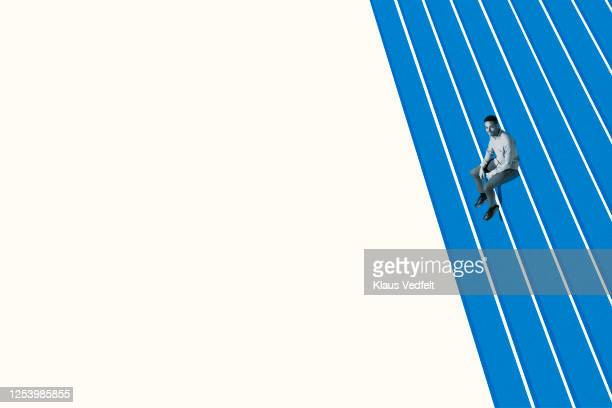 confident young man sitting on blue bleachers - oresund region stock pictures, royalty-free photos & images