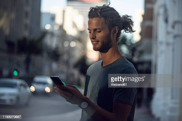 confident young man using smartphone in the city - one man only stock pictures, royalty-free photos & images