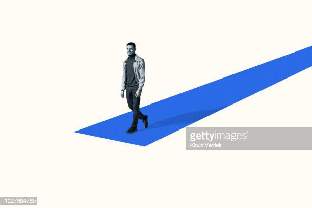 confident young man walking on blue ramp - catwalk stage stock pictures, royalty-free photos & images
