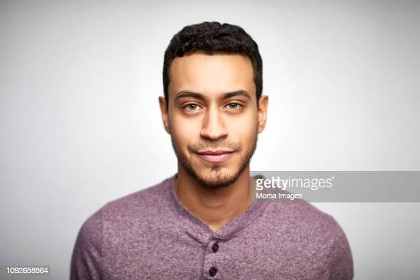 confident young man wearing purple t-shirt - mannen stockfoto's en -beelden