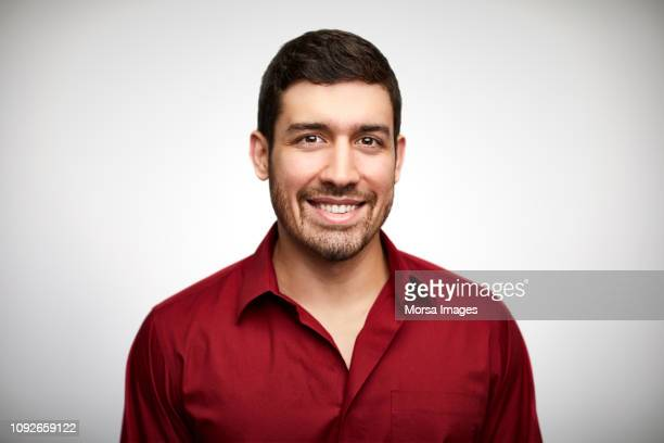 confident young man wearing red shirt - red shirt stock pictures, royalty-free photos & images