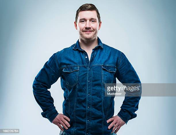 confident young man with hands on his hips - handen op de heupen stockfoto's en -beelden