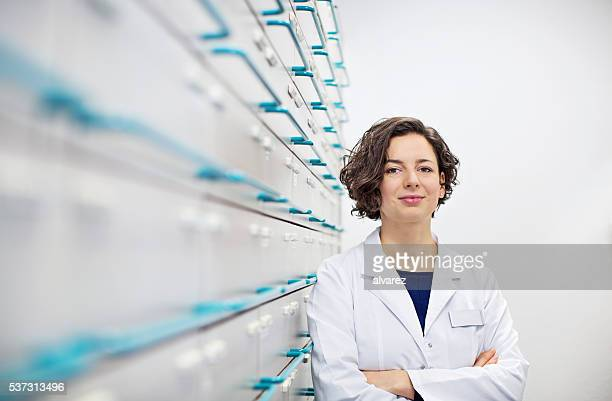 Confident young pharmacist standing by a medicine shelf