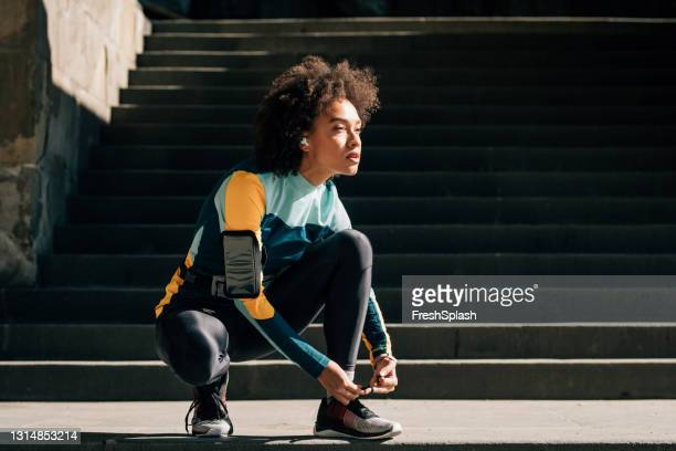 confident young sportswoman tying her shoelace, exhausted from a jog - black shoe stock pictures, royalty-free photos & images