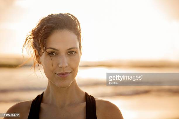 Confident young woman at beach during sunset