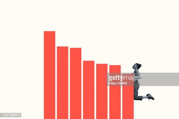confident young woman climbing orange bar graph - バイアス ストックフォトと画像