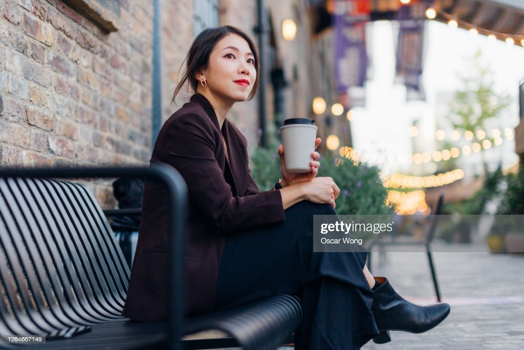 Confident Young Woman Drinking Coffee, Sitting At A Sidewalk Cafe : Stock Photo