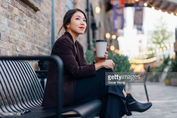 confident young woman drinking coffee, sitting at a sidewalk cafe - bench stock pictures, royalty-free photos & images