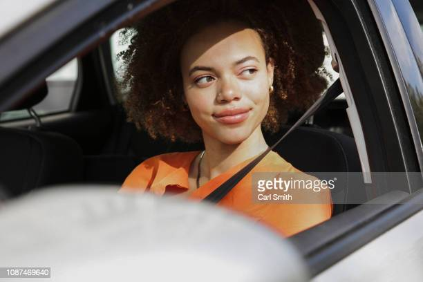 confident young woman driving car - driving stock pictures, royalty-free photos & images