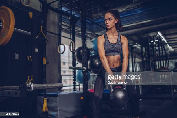 confident young woman exercising in gym - crossfit stock pictures, royalty-free photos & images