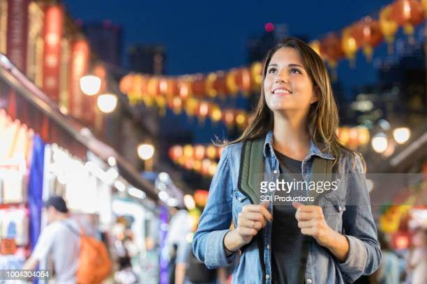 Confident young woman explores Singapore's Chinatown night life