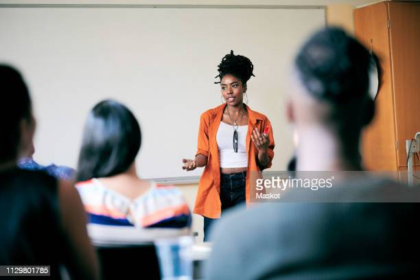 confident young woman gesturing while teaching students in class - education building stock pictures, royalty-free photos & images