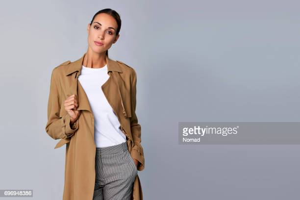 confident young woman holding brown trench coat - coat stock pictures, royalty-free photos & images