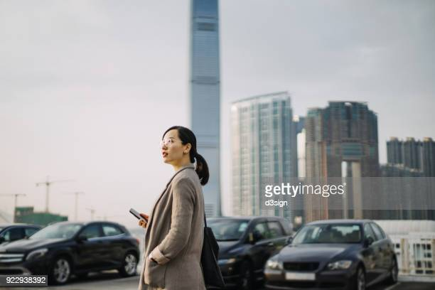 Confident young woman holding mobile phone in rooftop parking lot against modern cityscape
