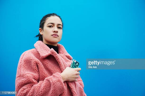 confident young woman holding smartphone. - medium shot stock pictures, royalty-free photos & images